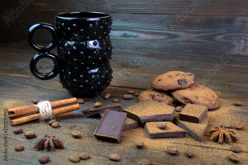 Black cup with biscuits and cinnamon on a brown board