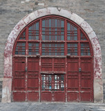 Beijing, China - April 26, 2010: Closeup of large bow-shaped maroon entrance door to under-belly of Bell Tower set in gray stone wall.