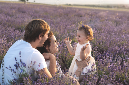 Beautiful young family, father and mother with little daughter playing on lavander field