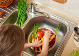 girl wash fruits and vegetables in home kitchen - healthy eating concept