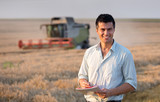 Engineer with notebook and combine harvester in field - 200306723