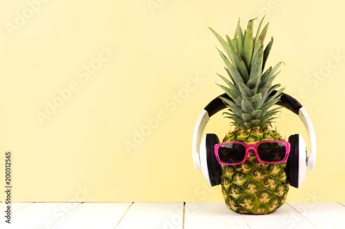Foto Murales Hipster pineapple with sunglasses and headphones against a yellow background. Minimal summer concept.