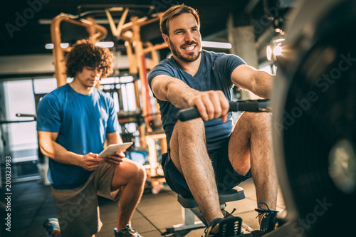 Poster Keep going! You can do it! Mid adult man with his personal instructor in fitness center. Rowing machine.