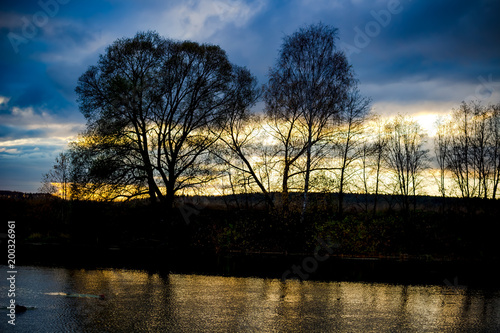 Sunset against the background of trees over the river  - 200326961