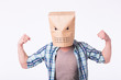 Man with cardboard box on his head and drawing of angry emoticon face. Angry man starting a fight.