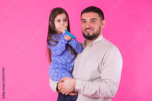 Happy father with his baby daughter on pink background - 200337131