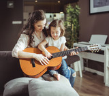 Mother and daughter playing a guitar - 200337361