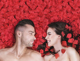Romantic couple laying on rose petals - 200338148