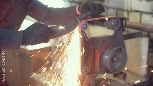Worker in workshop processing metal details