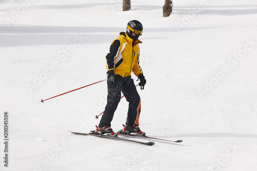 Poster Wit Adult skiing on a snowy hill landscape. Winter sport