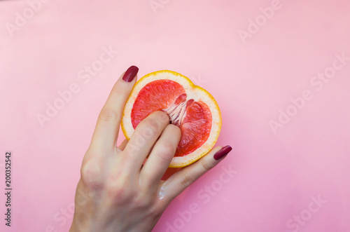 Two fingers on grapefruit on pink background. Sex concept. - 200352542