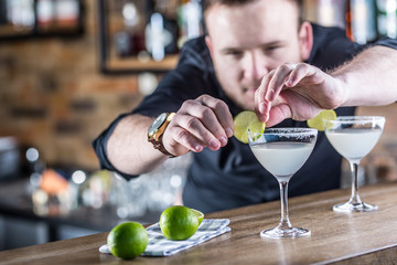 Barman in pub or restaurant preparing a cocktail drink margarita.