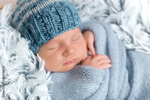Newborn infant sleeping in box among blue blankets