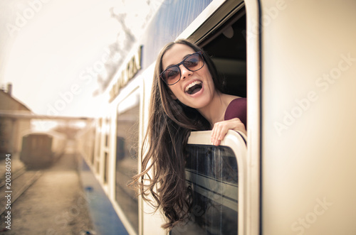 Fototapeta Excited girl traveling by train, looking out from the window