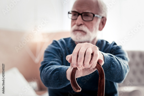 Senior age. Selective focus of elderly mans hands being put on the walking stick while holing it