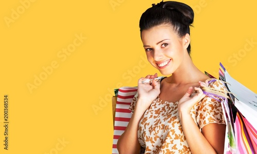 Woman with shopping bag on yellow background