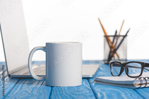 closeup shot of cup, eyeglasses on textbook, laptop and organizer with pens and pencils - 200368978