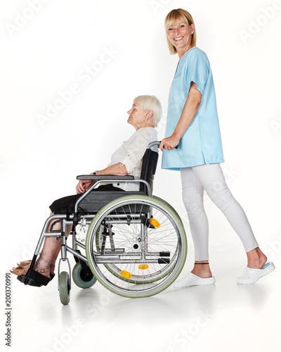 Foto Murales Pflegerin schiebt Seniorin im Rollstuhl