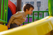 Cute caucasian child boy having fun to play slider in the playground