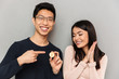Cheerful young asian loving couple holding bitcoin.