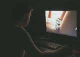 Man watching erotic movie on computer at night.