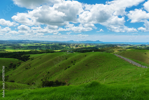 Fotobehang Natuur Rolling hills and meadows under a blue sky filled with clouds