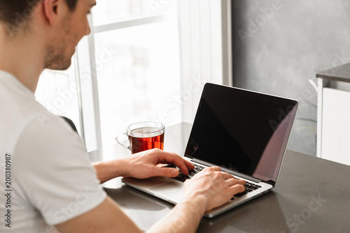 Photo from back of young man 30s in casual clothing typing on laptop, while working at home