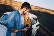 Young beautiful couple hugging each other, sitting on a small white car in beautiful evening light. Stylish guy with a beard and blond girl laughing