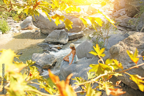 Leinwanddruck Bild A Young Girl Sits On A Stone In A Dress And A Hat On The Bank Of A Mountain River. Autumn leaves