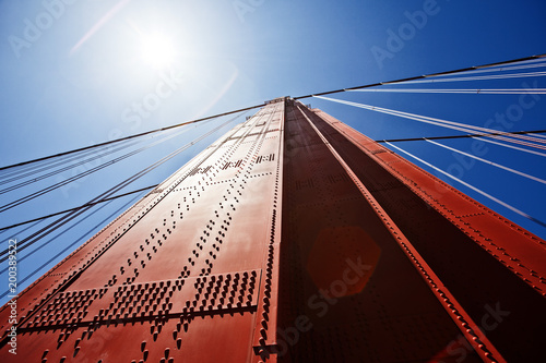 Plexiglas San Francisco Teil der Golden Gate Bridge in San Francisco aus der Froschperspektive mit Sonnenreflex