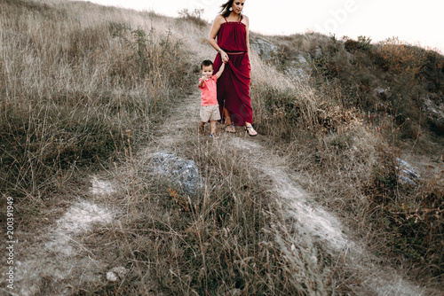 Plexiglas Grijs beautiful young mother in a long red dress easy walks with her young son. Summer, sunset, high yellow grass, mountains. He is on the hands, holding the hand