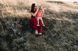 beautiful young mother in a long red dress with her little son walking on mountain sites on the sunset in summer, dry grass