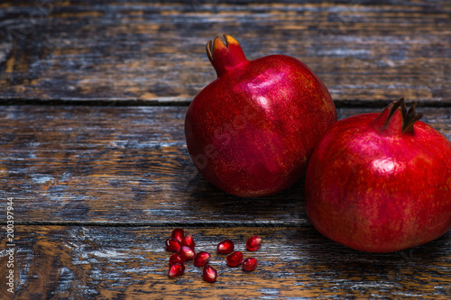Garnet red, ripe, juicy, whole and half of a pomegranate, grain, seeds on a wooden background
