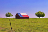 A barn on a Texas ranch with the state flag painted on the roof - 200399799