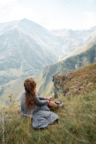 Beautiful young woman in a long dress is sitting on a cliff in the background of mountains