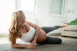 Sporty pregnant woman doing exercises at home