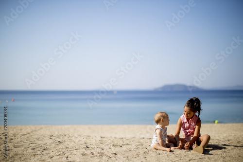 Śliczne małe siostry siedzi na plaży