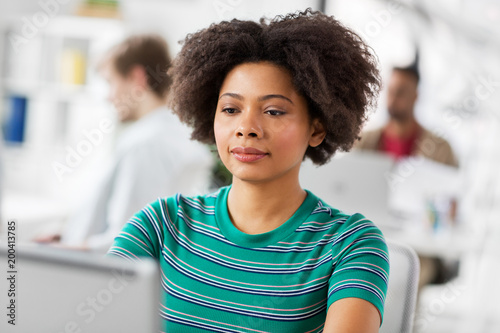 business, education and people concept - young african american woman with laptop computer working at office