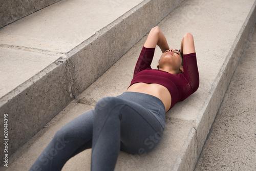 Dysponowany młody brunetki lying on the beach na schodkach
