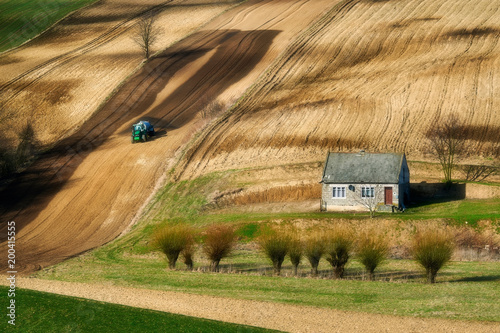 Foto Murales Farmer in tractor preparing land with seedbed cultivator, spirng, countryside in Ponidzie, Poland