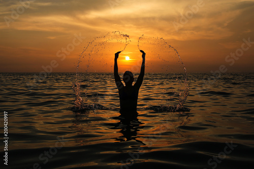 The girl splashes water against the setting sun in the sea - 200420997
