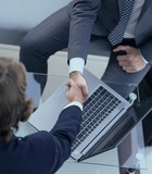 handshake of business partners above the Desk. - 200425549