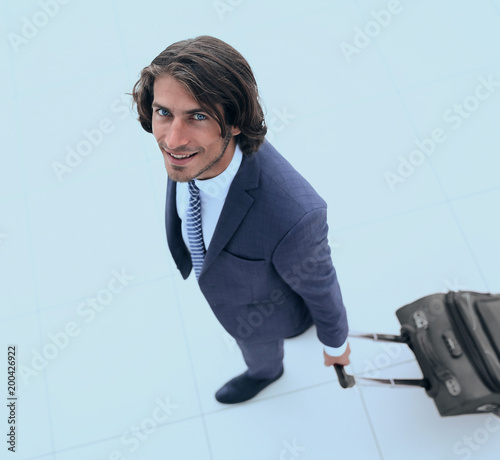 smiling businesswoman with travel suitcase