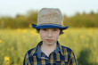 Portrait of a boy in a hat and shirt close-up.