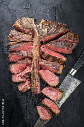 Fotobehang Steakhouse Barbecue dry aged wagyu porterhouse steak sliced as top view on a burnt board