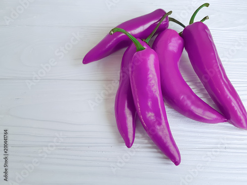 Plexiglas Hot chili peppers pink pepper on a white wooden backgrou