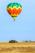 A multi-colored balloon is flying over a field in the sky near a farm