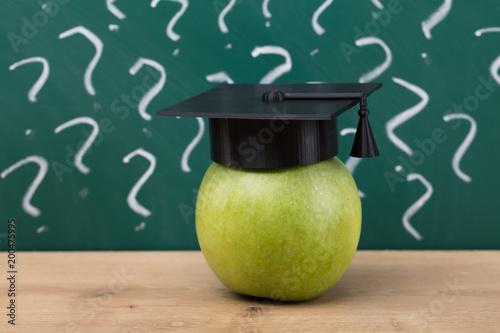 Foto Murales Green Apple With Graduation Hat On Wooden Desk