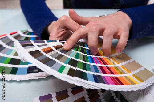 Designer Choosing Color From Color Swatches