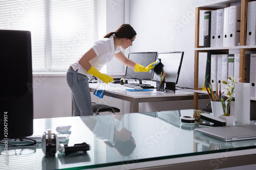 Woman Cleaning Computer In Office - 200479974